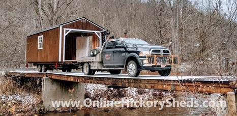 Hickory Shed being towed across an old bridge